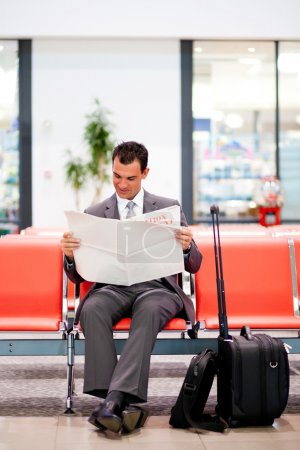 Businessman reading newspaper at airport