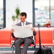 Young businessman reading newspaper at airport...