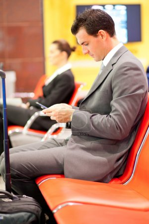 Businessman sending text messages at airport
