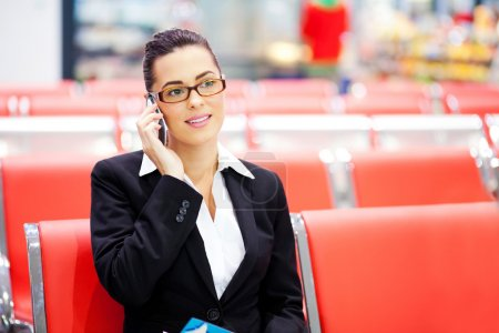 Businesswoman talking on cell phone at airport