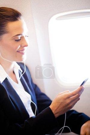 Businesswoman listening music on airplane