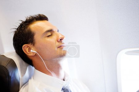 Tired businessman relaxing on airplane