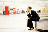 Businesswoman sitting on conveyor belt and waiting for her luggage