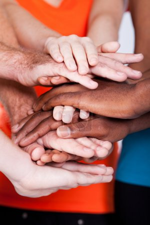 Multiracial group hands together