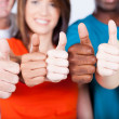 Group of multiracial friends thumbs up...