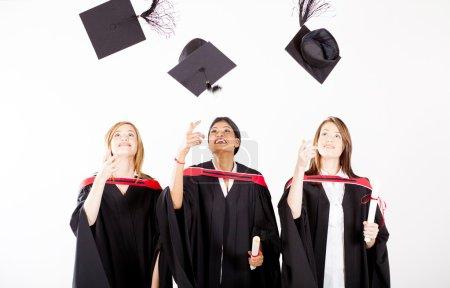 Group of female graduates throwing graduation cap