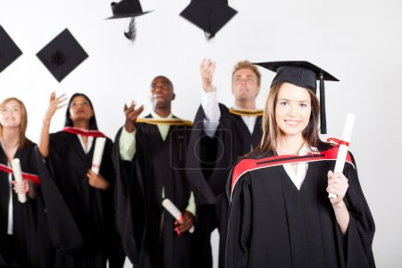 Photo for University graduate at graduation with classmates throwing caps in background - Royalty Free Image