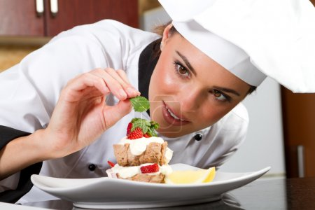Photo for Beautiful professional female chef decorating dessert - Royalty Free Image