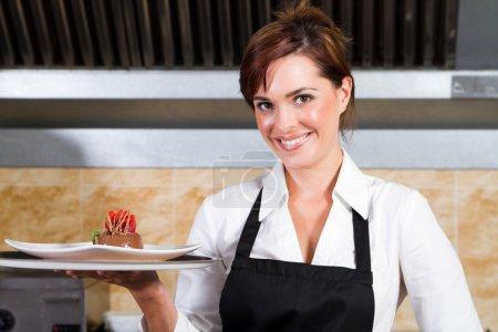 Photo for Pretty restaurant waitress presenting dessert - Royalty Free Image