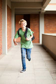 Middle school student running in school passage