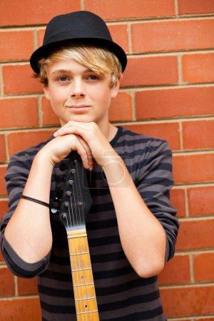 Photo pour Beau portrait de musicien adolescent avec guitare - image libre de droit