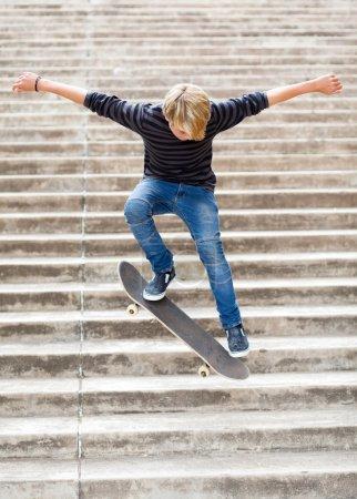 Photo pour Teen boy planche à roulettes dans les escaliers - image libre de droit