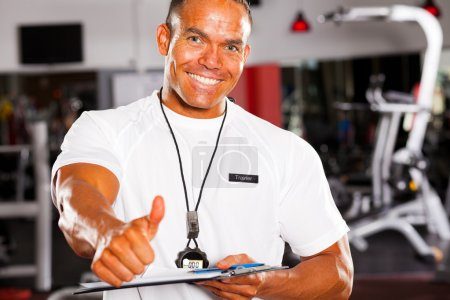 Male gym trainer giving thumb up