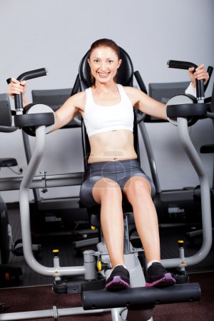 Fitness woman exercising with peck deck machine