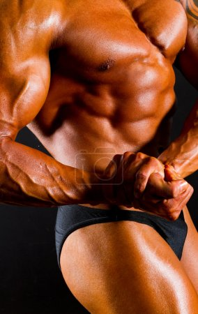 Photo for Male bodybuilder's body on black background - Royalty Free Image
