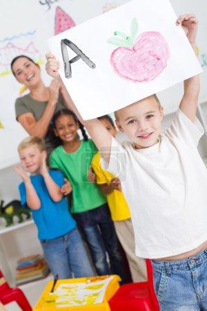Proud kindergarten boy holding painting high