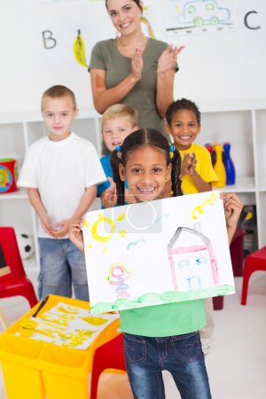 Proud kindergarten girl holding painting