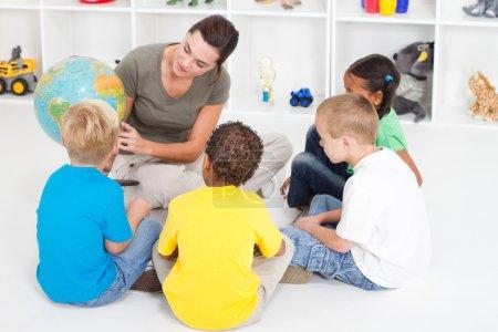Preschool teacher teaching kids about globe