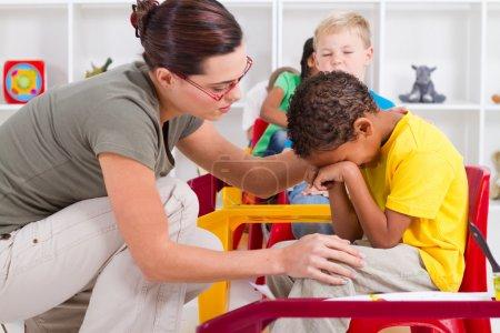 Photo for Teacher comforting crying preschool boy - Royalty Free Image