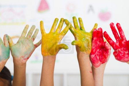las manos de niños cubren con pintura