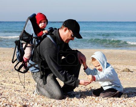 Photo pour Papa, fils et fille lors d'une promenade à la mer - image libre de droit