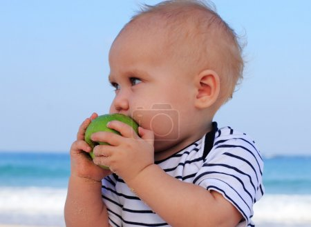 Child holding a green apple in the background sea