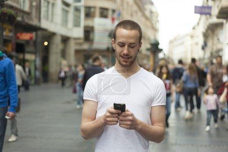Photo pour Jeune homme avec téléphone mobile à pied, fond est estompée ville - image libre de droit