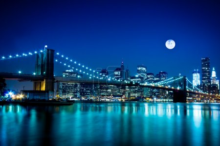 Photo for Night view of New York City and Brooklyn Bridge under a full moon - Royalty Free Image