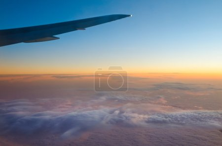 Photo for Wing of an airplane and low clouds - Royalty Free Image