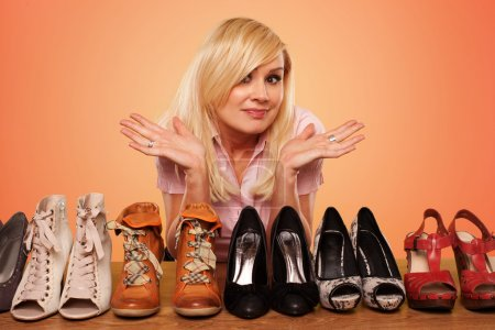 Photo for Beautiful Blonde trying to make a deccision about which pair of shoes to wear - Royalty Free Image