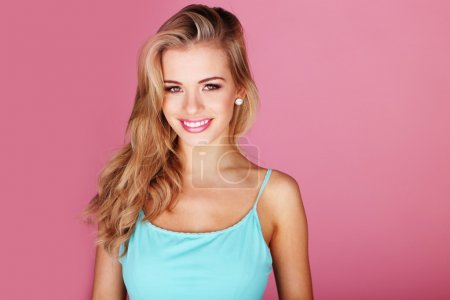 Photo for Pretty young woman smiling against a pink background - Royalty Free Image