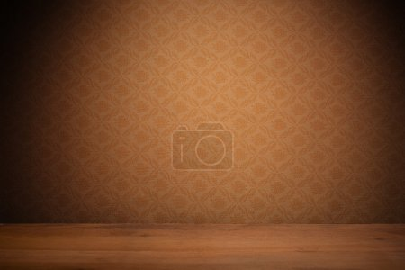 Photo for Vintage textured brown wallpaper with heavy vignetting over a wooden floor, empty with copyspace. - Royalty Free Image
