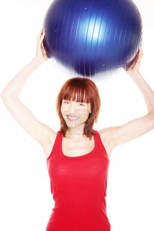 Photo for Smiling redhead woman in red summer dress holding a pilates ball above her head with both hands - Royalty Free Image