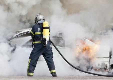 A firefighter putting out a car that was burning...
