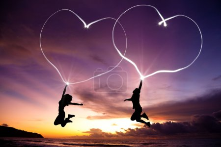 Photo for Young couple jumping and drawing connected hearts by flashlight in the air on the beach before sunrise - Royalty Free Image