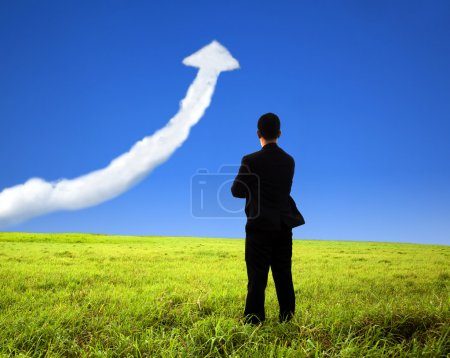 Photo for Business man stand on the field and watch growth graph cloud - Royalty Free Image