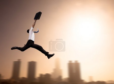 Photo for Excited Businessman running with cityscape background at morning - Royalty Free Image
