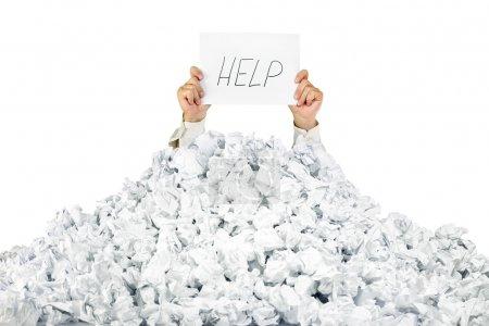 Foto de Persona bajo montón arrugado de papeles con la mano sosteniendo un signo de ayuda / aislado en blanco - Imagen libre de derechos