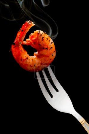 Photo pour Crevettes fumantes sur une fourchette sur fond noir - image libre de droit