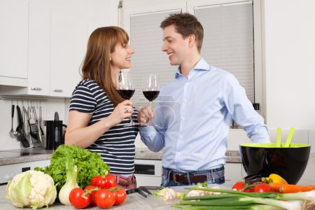 Photo for Photo of a young couple preparing salad in their kitchen and drinking wine. - Royalty Free Image