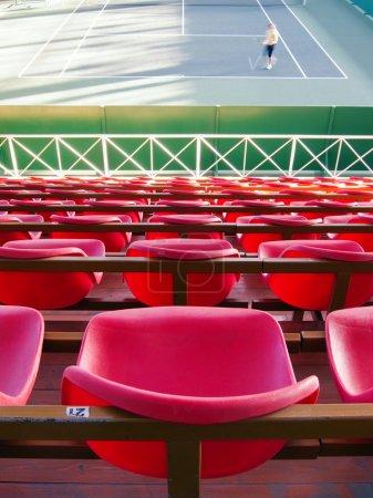Photo pour Tribune vide avec des sièges rouges sur un court de tennis - image libre de droit