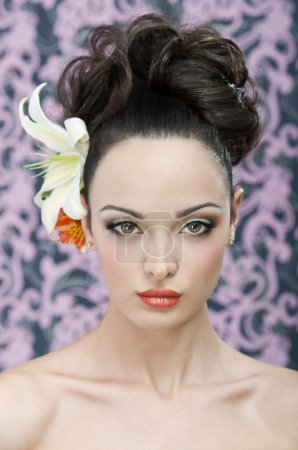 Photo pour Gros coup de tête beauté de 20 yeared jeune femme adulte avec le maquillage, les cheveux style et lily fleurs dans les cheveux. Salut-end retouche sauf petit et estompée, battant les poils autour de la tête - image libre de droit