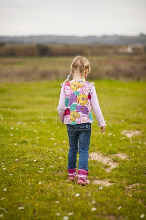 Photo for Cute little girl walking on a green field with flowers - Royalty Free Image