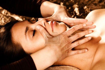 Foto de Mujer recibiendo masaje facial profesional en salón de spa - Imagen libre de derechos