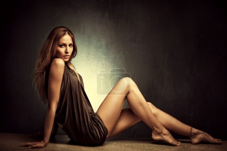 Photo for Young woman in elegant short dress sit barefoot, full body shot, studio shot - Royalty Free Image