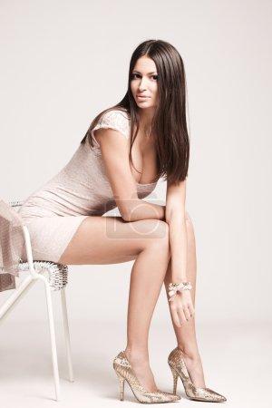Photo pour Elégante jeune femme en robe courte et talons hauts, plan studio - image libre de droit