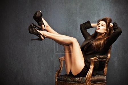 Photo pour Jolie femme en talons hauts, short et veste de smoking noir assis sur une chaise, cigarette dans la bouche, cheveux longs bruns, petite quantité de grain ajouté - image libre de droit