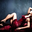 Elegant sensual young woman in red dress on recamier indoor shot