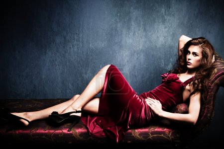 Sensual elegant young woman in red dress on recami...