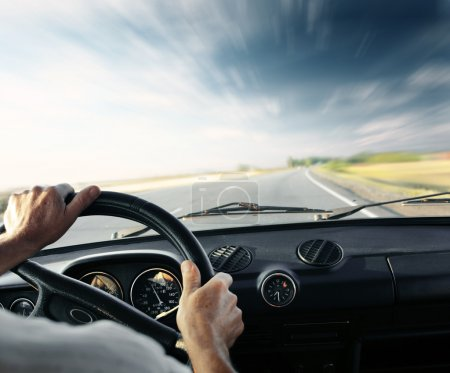 Photo pour De conduire les mains sur un volant d'une voiture et un ciel bleu avec des nuages flous - image libre de droit